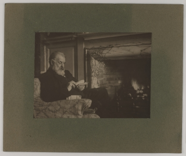 Photograph of Joseph Joachim reading letters in front of a fire. Mounted on card